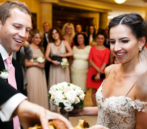 Happy newlywed bride and groom at wedding reception eating and drinking with guests